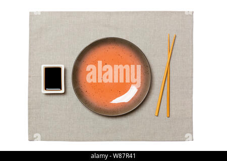 Empty round brown plate with chopsticks for sushi and soy sauce on grey napkin background. Top view with copy space for you design. - Stock Photo