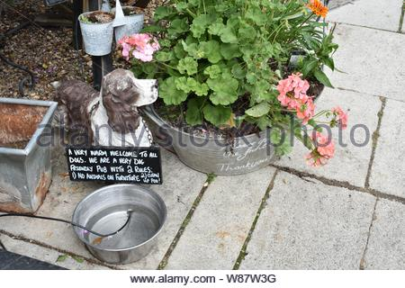 Water bowl, dog figure and notice outside The Flemish Weaver in Corsham. Sign reads: A very warm welcome to all dogs, we are a very dog friendly pub. - Stock Photo