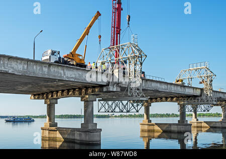 Overhaul of road transport bridge across the river in spring sunny day - Stock Photo