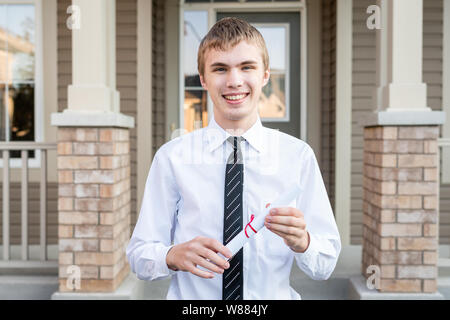 Young male student holding a diploma in front of a house while wearing a dress shirt and a tie. - Stock Photo