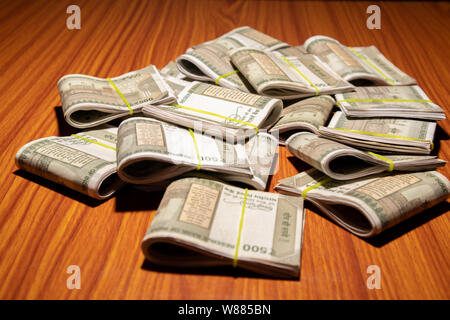 Concept of black money showing Pile of Indian currency on table in dark room. - Stock Photo
