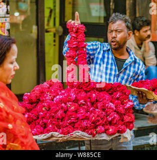Vrindavan, India - February 22, 2018 - Man sells red flower leis from his street table - Stock Photo