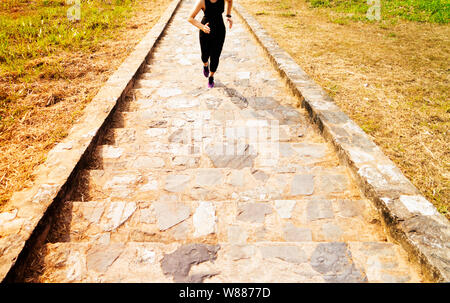 young sport woman running outdoor upstairs on blue sky - Stock Photo