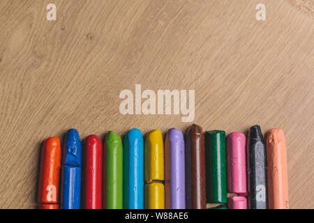 Colourful used crayons in a row on a wooden surface