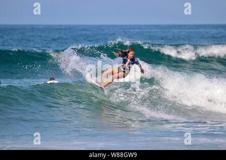 Professional French surfer Pauline Ado surfing off the coast of Huntington Beach, California - Stock Photo
