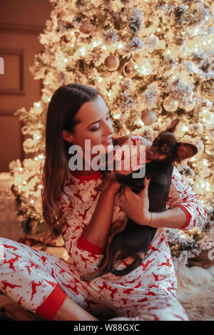 Young mother and her son in festive pajamas during Christmas event - Stock Photo