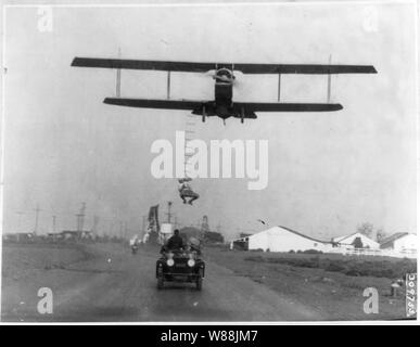 Fearless Freddie, a Hollywood stunt man, clinging to a rope ladder slung from a plane flown by A.M. Maltrup, about to drop into automobile below: automobile shown - Stock Photo