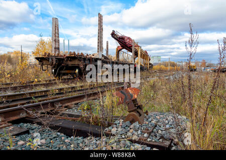 An old railway track laying machine stands on an abandoned old railway line. - Stock Photo