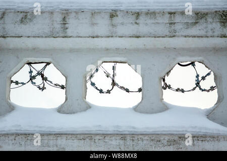 Barbed wire is visible in the holes of the concrete fence. - Stock Photo