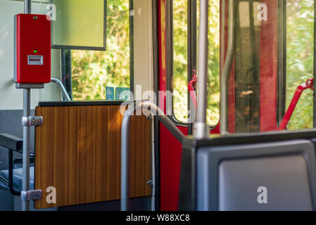 Red public transportation ticket stamp or validation ticket machine in front of the door inside tram or train passenger car. - Stock Photo