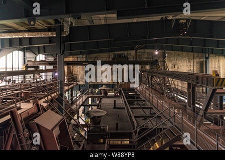 Typical interior view of former abandon coal mine industrial building and old rusty coal-washing plant and machine at Ruhr museum Zeche Zollverein. - Stock Photo