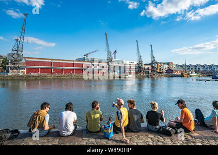 People sitting at the river area on a hot summers day in Bristol, England - Stock Photo
