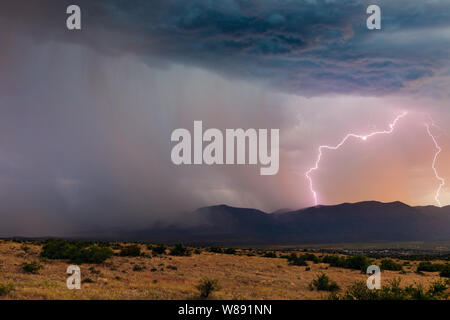 Lightning strikes Mingus Mountain as a strong, monsoon thunderstorm moves across the Verde Valley near Cottonwood, Arizona, USA. Stock Photo