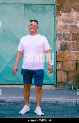 Senior tourist athletic middle eastern man walking on street,enjoying beautiful view old city.Traveling,freedom,active lifestyle concept.Business smiling mature man in shorts and t-shirt on vacation. - Stock Photo