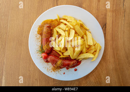 Currywurst, grilled pork sausage on top with curry powder served with curry ketchup sauce and Fried potatoes. - Stock Photo