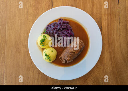 Rinderroulade, Beef roll or roulades, traditional German meal, serve with pickled red cabbage, dumplings potatoes and sauce on white plate . - Stock Photo