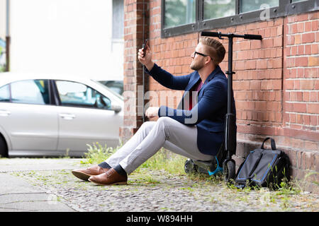 Smiling Businessman Sitting On Electric Scooter Near Brick wall Taking Selfie With Mobile Phone - Stock Photo