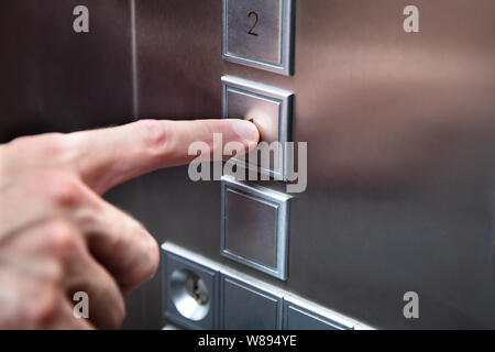Close-up Of Human Finger Pressing Elevator Button - Stock Photo