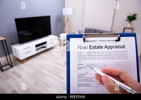 Close-up Of A Person's Hand Filling Real Estate Appraisal Form With Pen - Stock Photo