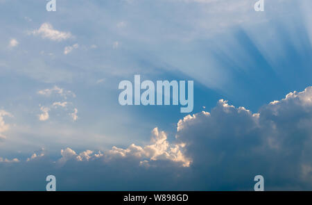 Optimistic sunset rays behind the clouds. Glow in the sky. Symbol of light. Beautiful scene of nature. - Stock Photo