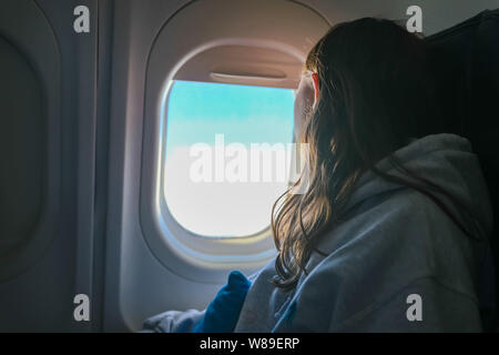 Girl looking out airplane window in flight while traveling - Stock Photo