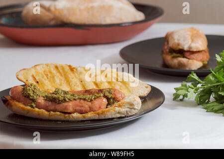 Choripan, south American style chorizo sandwich made with Argentine chorizo sausage with chimichurri, a parsley and olive oil based condiment - Stock Photo