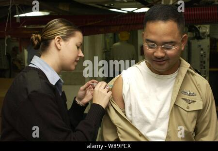 Petty Officer 3rd class Tiffany Long administers the influenza vaccination to Chief Petty Officer Romeo Mortel aboard the USS Kitty Hawk (CV 63) on Oct. 28, 2004. The immunizations are provided to all active-duty personnel to prevent the spread of the flu and maintain service members' health.  Long serves as a hospital corpsman and is from San Diego, Calif.  Mortel is assigned as a personnel man and is from Batangas, Philippines.
