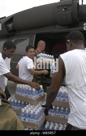 U.S. Navy sailors and U.S. Army National Guard members load water and ice into a UH-60 Black Hawk helicopter at Gulf Port International Airport in Biloxi, Miss., on Sept. 1, 2005.  Department of Defense units are mobilized as part of Joint Task Force Katrina to support the Federal Emergency Management Agency's disaster-relief efforts in the Gulf Coast areas devastated by Hurricane Katrina.  The airport is now one of the main staging areas for hurricane-relief efforts in Mississippi.  The sailors are from the USS Bataan (LHD 5) that is operating in the Gulf of Mexico approximately 100 miles sou - Stock Photo