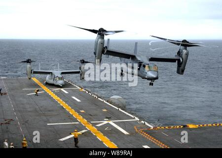 A U.S. Marine Corps MV-22B Osprey executes a vertical take off from the flight deck of the amphibious assault ship USS Wasp (LHD 1) as another waits to launch during flight operations in the Atlantic Ocean on Nov. 15, 2005.  The Osprey is an advanced technology, vertical/short takeoff and landing multipurpose tactical aircraft and is scheduled to replace the aging CH-46E Sea Knight and CH-53D Sea Stallion helicopters currently in service.  These Ospreys are assigned to Marine Tiltrotor Operational Test and Evaluation Squadron 22 of Marine Corps Air Station New River, N.C. - Stock Photo