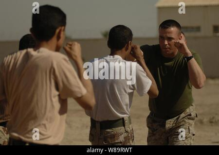 U.S. Marine Corps Staff Sgt. Joseph Kepler teaches Iraqi army soldiers how to properly throw a punch during hand-to-hand combat training in Husiniyah, Iraq, on April 4, 2006. - Stock Photo