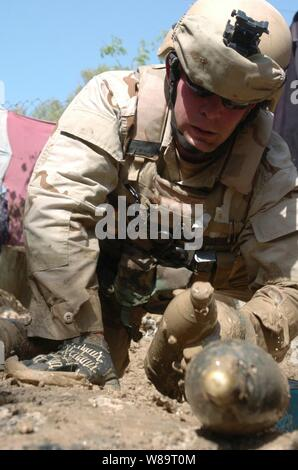 U.S. Navy Petty Officer 2nd Class William Schofer pulls ordnance buried in the mud near an abandoned building in Baghdad, Iraq, on April 20, 2006.  Schofer and his fellow Explosive Ordnance Disposal Mobile Unit Six sailors recovered 340 anti-personnel mines and mortar shells from the site. - Stock Photo