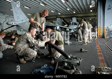 U.S. Marines perform maintenance on their equipment in the hangar bay of the USS Boxer (LHD 4) as the ship operates in the Pacific Ocean on Aug. 15, 2006.   The Marines are part of Weapons Company, 2nd Battalion, 4th Marines, attached to the 15th Marine Expeditionary Unit.
