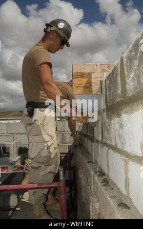 U.S. Navy Seabee Petty Officer 3rd Class Bradley Clark smoothes mortar as he builds a wall for a girl's school dormitory in Tadjoura, Djibouti, on Jan. 10, 2007.  Clark is a Navy builder with Naval Mobile Construction Battalion 5 attached to Combined Joint Task Force-Horn of Africa. - Stock Photo