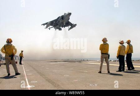 U.S. Navy flight deck crewmembers watch a Marine AV-8B Harrier land on the flight deck of the amphibious assault ship USS Bonhomme Richard (LHD 6) while under way in the Persian Gulf on Sept. 15, 2007.  The vertical/short takeoff and landing jet is attached to the Marine Expeditionary Unit 13, Air Combat Element. - Stock Photo