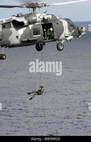 A U.S. Navy explosive ordnance disposal technician repels from an HH-60H Sea Hawk helicopter onto the flight deck of the aircraft carrier USS Nimitz (CVN 68) during a routine training exercise while under way in the East China Sea on March 15, 2008.   The technician is assigned to Explosive Ordnance Disposal Mobile Unit 11. - Stock Photo