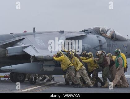U.S. Navy crewmembers push an AV-8B Harrier aircraft onto an aircraft elevator aboard the Wasp class amphibious assault ship USS Essex (LHD 2) on April 29, 2008.  The Essex is the lead ship of a forward ñdeployed U.S. Expeditionary Strike Group. - Stock Photo