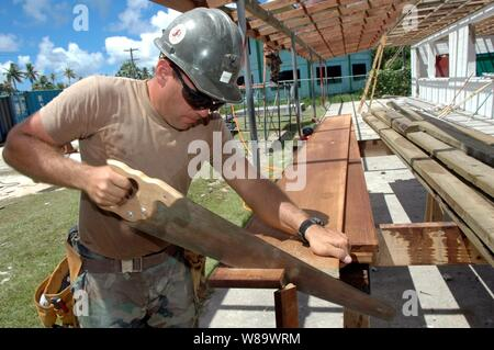 U.S. Navy Petty Officer 2nd Class Gabriel Kelley of Navy Mobile Construction Battalion 133 cuts wood planks for the reconstruction of Mwan Elementary School during a Pacific Partnership engineering civic action program in Chuuk, Federated States of Micronesia, on Aug. 23, 2008.  The Pacific Partnership construction team is assisting five different countries, renovating schools, hospitals, and medical clinics. - Stock Photo