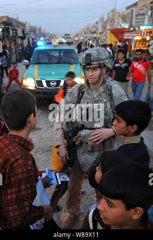 U.S. Air Force 1st Lt. Steven Benson speaks with Iraqi children during a patrol with Iraqi police in the Shurta Market of the Al-Bayaa district of Baghdad, Iraq, on Nov. 14, 2008.  The airmen are assigned to Detachment 3, 732nd Expeditionary Security Forces Squadron and are attached to the 1st Brigade Combat Team, 4th Infantry Division. - Stock Photo