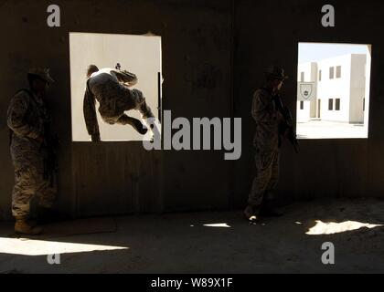 U.S. Marine Corps Lance Cpls. Travis Beckford (left) and Kyle Nance and Cpl. Ryan Burke (right), all from the 4th Platoon, Fleet Anti-terrorism Security Team, advance through buildings during a bilateral urban assault training in Sheik Isa, Bahrain, on Nov. 20, 2008.  The Marines are deployed to the U.S. Navy 5th fleet area of operations in support of maritime security operations. - Stock Photo