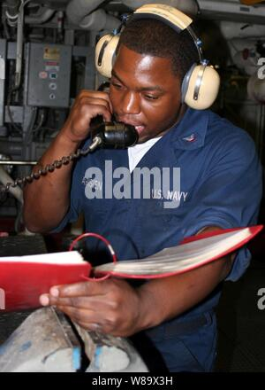 U.S. Navy Petty Officer 3rd Class Paris Pharisien gives a status report during a roving watch aboard the amphibious transport dock ship USS San Antonio (LPD 17) underway in the Persian Gulf on Dec. 2, 2008.  The San Antonio is deployed with the Iwo Jima Expeditionary Strike Group to support maritime security operations in the U.S. 5th Fleet area of responsibility. - Stock Photo