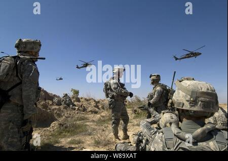U.S. Army soldiers wait to be picked up by helicopters south of Balad Ruz, Iraq, on March 22, 2009.  The soldiers are assigned to Recon Platoon, 1st Battalion, 24th Infantry Regiment, 1st Stryker Brigade Combat Team, 25th Infantry Division. - Stock Photo