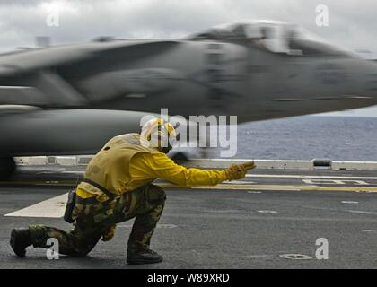 U.S. Navy Petty Officer 1st Class Michael Quintos launches an AV-8B Harrier aircraft during the fly off of Marine Attack Squadron 211, 31st Marine Expeditionary Unit from the flight deck of the amphibious assault ship USS Essex (LHD 2) in the Philippine Sea on Aug. 10, 2009. - Stock Photo