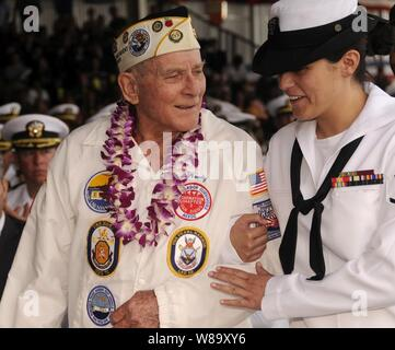 Woody Derby, a Pearl Harbor survivor, escorted by U.S. Navy Petty Officer 3rd Class Kathleen McDowell honors the USS Nevada (BB 36) as they celebrate Pearl Harbor Day at Pearl Harbor, Hawaii, on Dec. 7, 2009.  The National Park Service and the U.S. Navy are hosting a joint memorial ceremony with more than 2,000 distinguished guests, the general public and military personnel, both active and retired, to commemorate the 68th anniversary of the attack on Pearl Harbor.  The theme of the ceremony was 'But Not in Shame: The Aftermath of Pearl Harbor.' - Stock Photo