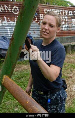 U.S. Navy Petty Officer 2nd Class Alicia Williamson, embarked aboard the multipurpose amphibious assault ship USS Iwo Jima (LHD 7), removes rust from a swing set during a community service project at Las Carmeles Park in Bluefields, Nicaragua, on Sept. 20, 2010.  The ship is supporting the humanitarian civic assistance mission Continuing Promise 2010. - Stock Photo