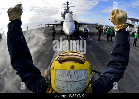 An aircraft director guides an F/A-18C Hornet onto a catapult aboard the aircraft carrier USS Harry S. Truman (CVN 75) in the Atlantic Ocean on Feb. 1, 2011.  The Harry S. Truman is supporting fleet replacement squadron carrier qualifications. - Stock Photo