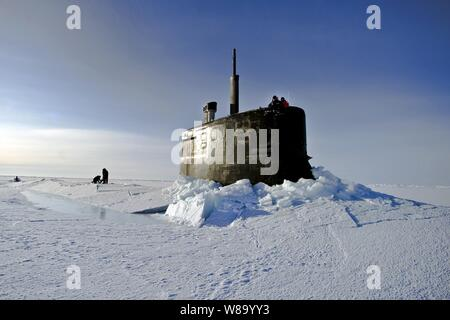U.S. Navy sailors and members of the Applied Physics Laboratory Ice Station clear ice from the hatch of the USS Connecticut (SSN 22) as it surfaces above the ice in the Arctic Ocean on March 19, 2011.  The submarine and crew are participating in Ice Exercise 2011, which tests submarine operations in the Arctic. - Stock Photo