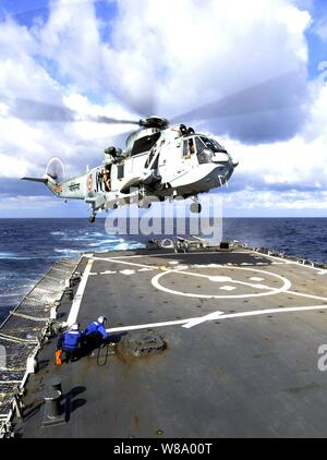 U.S. Navy flight crew members aboard the guided missile destroyer USS Stethem (DDG 63) prepare to tie down an Indian navy MK42 Sea Hawk helicopter as it lands on the shipís flight deck while underway in the Philippine Sea on April 5, 2011.  The operation was part of the joint exercise Malabar 2011, a series of training events designed to advance multinational maritime relationships and mutual security issues. - Stock Photo