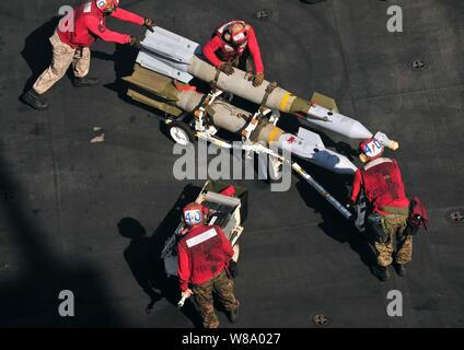 Marines assigned to the aircraft carrier USS Enterprise (CVN 65) push ordnance into place to arm an F/A-18C Hornet assigned to Attack Squadron 251 while underway in the Arabian Sea on March 26, 2011.  The Enterprise and Carrier Air Wing 1 are conducting maritime security operations and close-air support missions for Operation Enduring Freedom in the U.S. 5th Fleet area of responsibility. Stock Photo