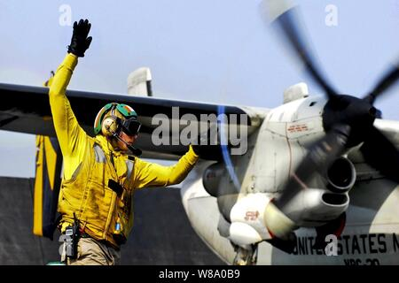 U.S. Navy Lt. Jerrod Washburn signals the launch of a C-2A Greyhound from the aircraft carrier USS Ronald Reagan (CVN 76) in the Arabian Sea on June 30, 2011.  Washburn is a flight deck shooter.  The Greyhound is assigned to Fleet Logistics Combat Support Squadron 30. - Stock Photo