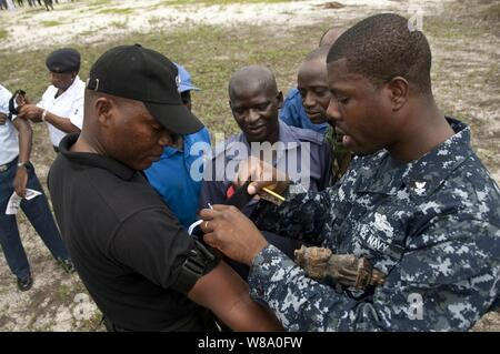 U.S. Navy Petty Officer 2nd Class Eseosa Osemwota (right) instructs a group of Nigerian service members on the proper application of a tourniquet during a tactical combat casualty care course as part of Africa Partnership Station West in Lagos, Nigeria, on Aug. 2, 2011.  Africa Partnership Station is an international security cooperation initiative facilitated by Commander, U.S. Naval Forces Europe-Africa aimed at strengthening global maritime partnerships through training and collaborative activities in order to improve maritime safety and security in Africa. - Stock Photo